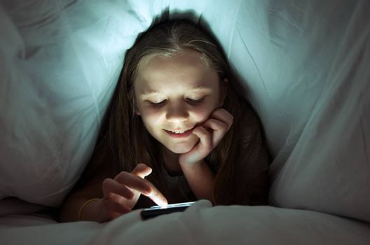Young girl using a phone in bed