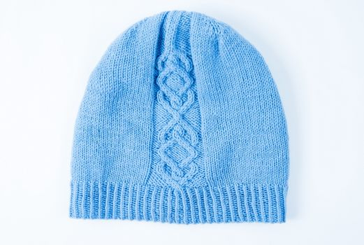 Knitted winter hat on the white