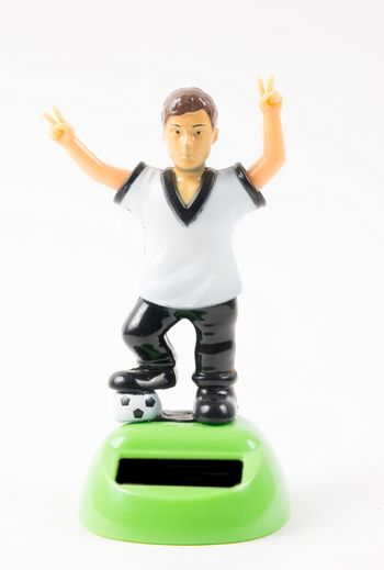 Plastic toy of the soccer player on the white