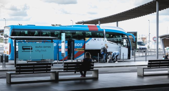 Faro, Portugal - May 3, 2018: Passengers boarding a City-Bus bus in the car park of Faro International Airport on a spring day
