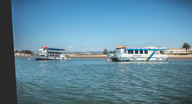 Tavira, Portugal - May 3, 2018: Tourist transport boats moored in the lagoons of the Ria Formosa Natural Park near the port of Tavira on a spring day