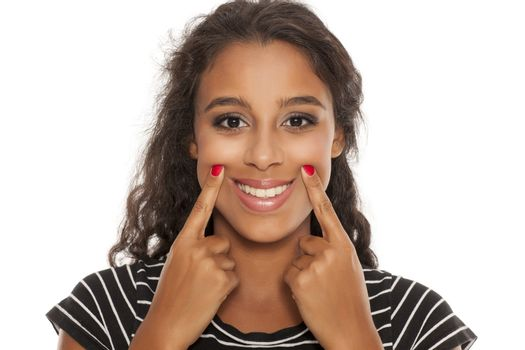 dark skinned woman forsed her smile with her fingers