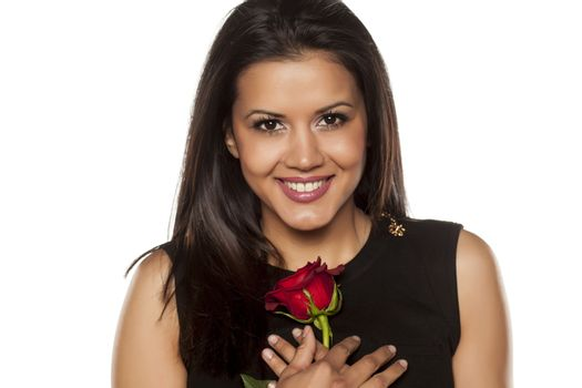 happy beautiful young woman holding a red rose on white background