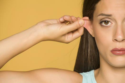 woman pulling her ear