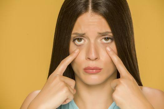 woman touching her  low eyelids