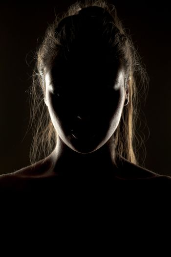 Mysterious portrait of woman in shadow