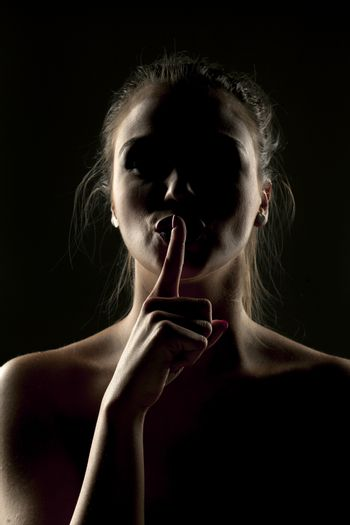Mysterious portrait of woman in shadow with finger on her lips