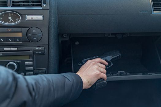 the driver takes the gun from the passenger compartment of the car. Gangster or policeman
