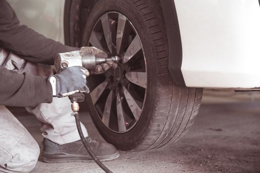 screwing the wheel to the car using a pneumatic screwdriver. Replacement of seasonal tires in a car repair shop