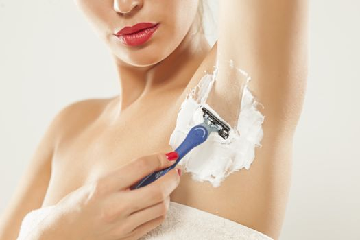 Young woman shaves her armpit