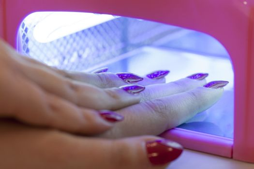 drying the nail polish with uv lamp