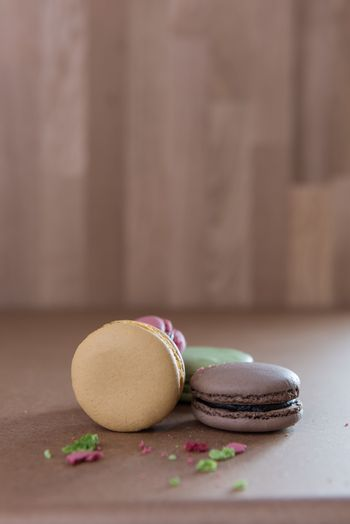 French broken sweet delicacy macaroons on wood background