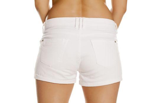 Female bottom in white short jeans