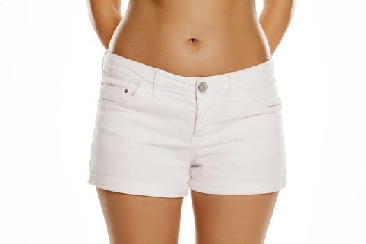 Female hips in white short jeans
