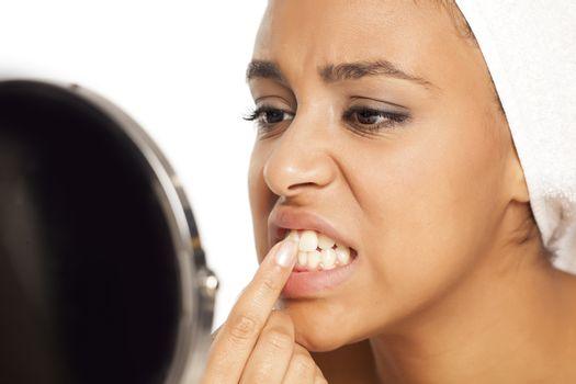 portrait of young dark-skinned woman picking her teeth with finger on white background