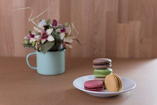 French sweet delicacy macaroons and flower vase on grunge wood t
