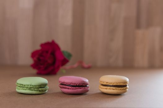 French sweet delicacy macaroons and red rose on grunge wood tabl