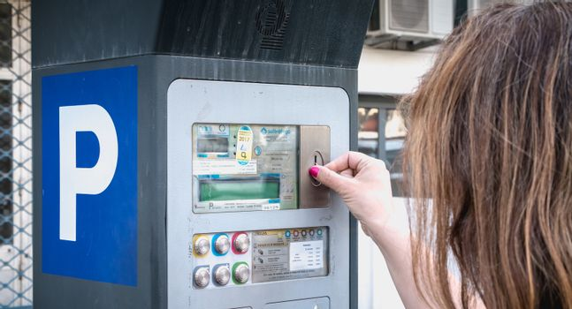 Albufeira, Portugal - May 3, 2018: Woman in front of a parking ticket machine paying her parking in the city center on a spring day