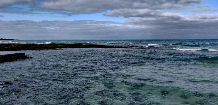 Cobalt blue sea hitting ancient volcanic rocks on Hyeopjae beach