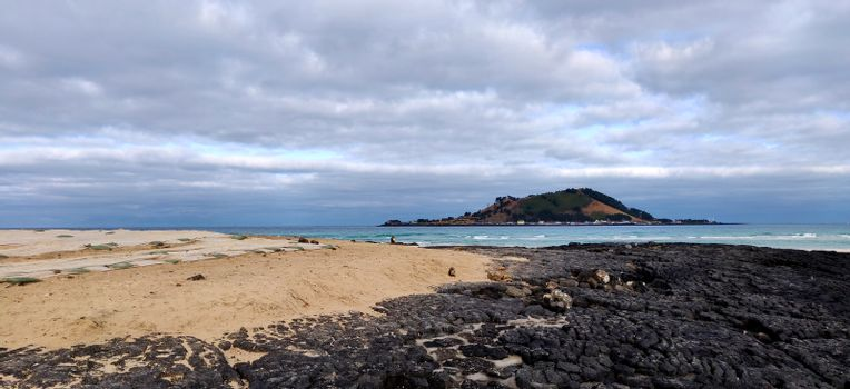 Black volcanic rock in Hyeopjae beach with mountain and cobalt blue sea