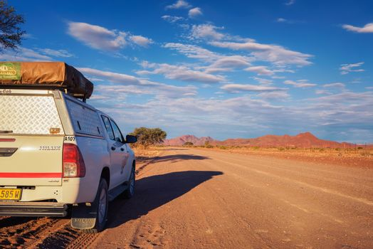 4x4 rental car equipped with a roof tent parks on a dirt road in Namibia