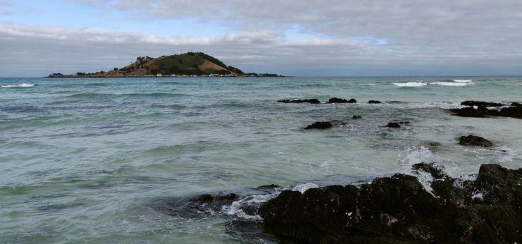 Waves in cobalt blue sea with black volcanic rocks
