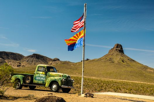 Vintage car in the arizona desert with national and state flags