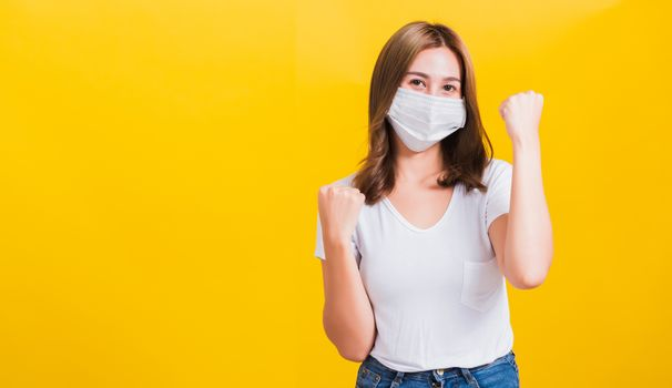 Asian beautiful happy young woman wearing face mask protection filter dust pm2.5, COVID virus and air pollution her raise hands glad excited cheerful after recovering from illness on yellow background