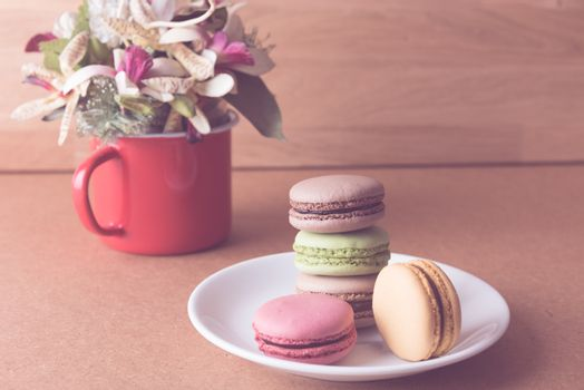 Retro French sweet delicacy macaroons and red coffee cup on wood
