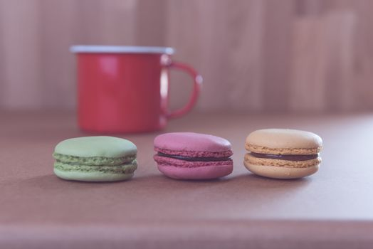 Vintage French sweet delicacy macaroons and red coffee cup on wo