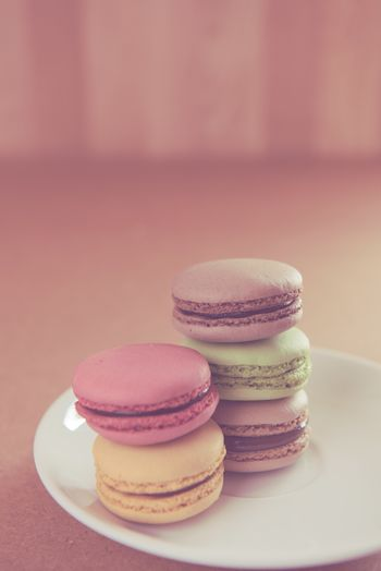 Vintage French sweet delicacy macaroons on wood background