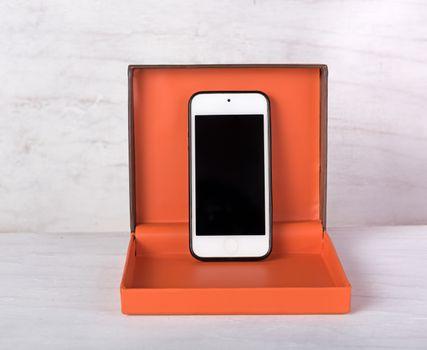 Smartphone in orange gift box on grunge white background