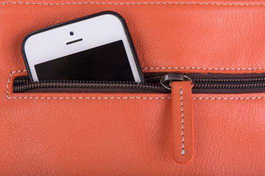 Mobile phone in orange leather pocket