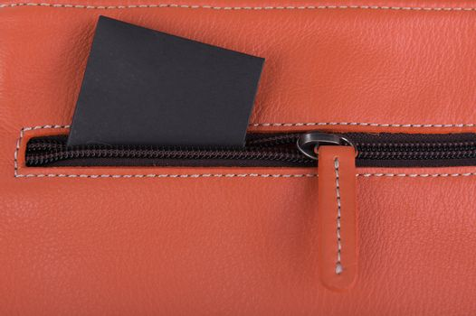 Close up orange leather bag with black label
