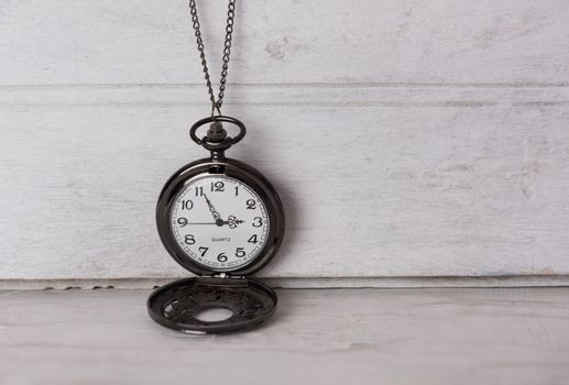 Classic pocket watch on white grune wooden background