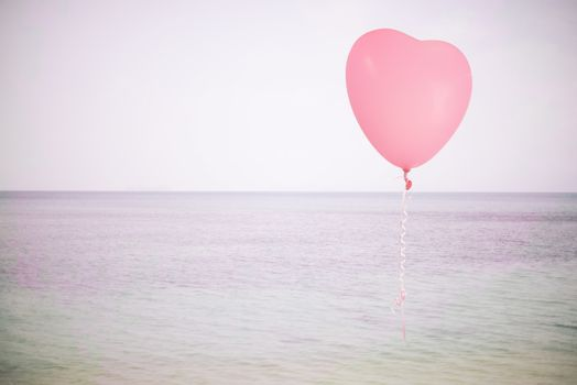 Grunge pink balloon over sea sky background with retro filter effect