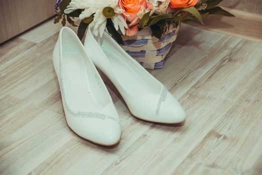 Beautiful white bride wedding shoes and bouquet in the basket