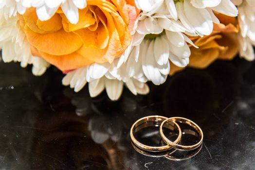 Two beautiful wedding rings lie on a wedding bouquet of orange roses and white colors.