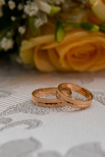 Two beautiful gold wedding rings lie on the table near the bouquet of orange roses and white flowers.