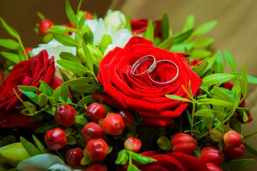 Two gold wedding rings lying on a red rose