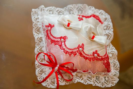 Beautiful wedding rings lie on a cushion with red and white lace.
