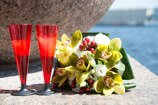 Beautiful wedding bouquet of orchids and two red glass of champagne on the background of water.