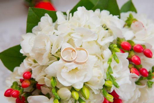 Two gold wedding rings lie on a bouquet with white flowers and red berries
