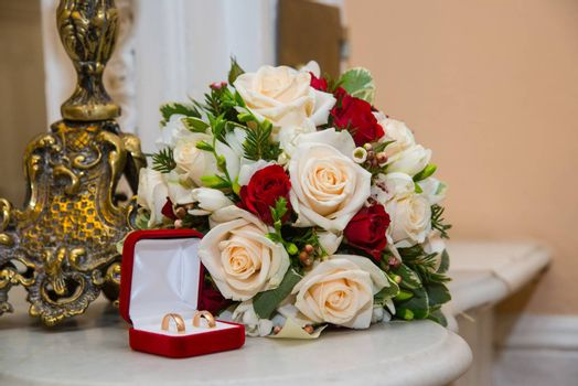 Two beautiful wedding gold rings with diamonds are in the red box near the bride's bouquet of red and white roses.