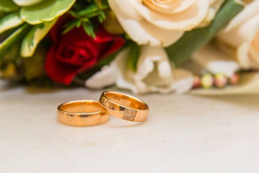 Two beautiful wedding gold rings with diamonds are about the bride's bouquet of red and white roses.