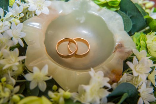 Two beautiful gold wedding rings for the couple lie on a saucer with flowers.