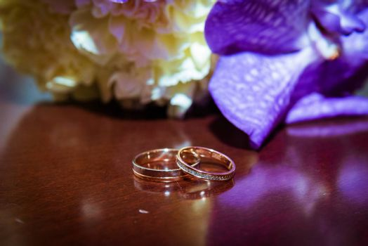 Two beautiful gold wedding rings lie on a bouquet.