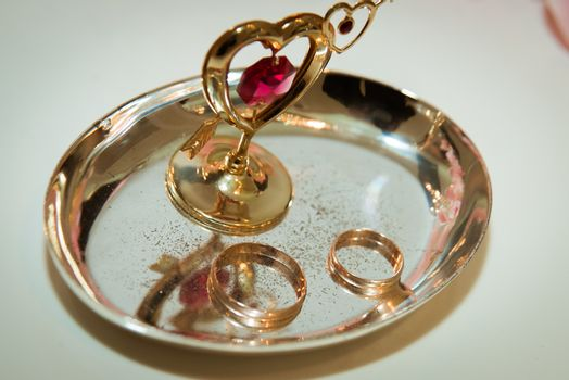 Two beautiful gold wedding rings lie on plates decorated with the heart