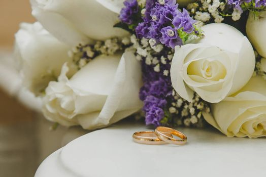 Two beautiful gold wedding rings lie on a bouquet on wedding day