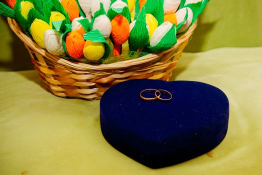 Two beautiful gold wedding rings lie on a bouquet.Box in the shape of a heart.